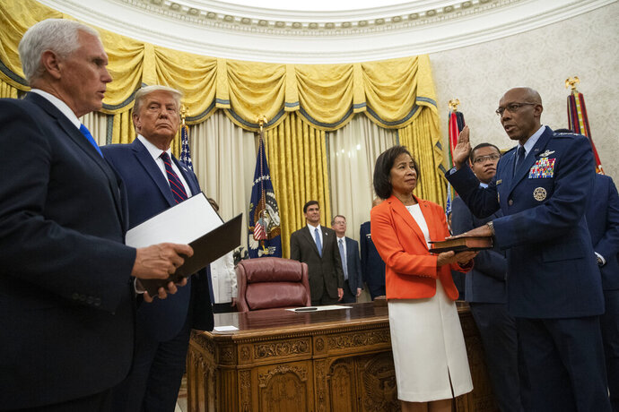 President Donald Trump, watches as Vice President Mike Pence swears in Gen. Charles Q. Brown Jr., as Chief of Staff of the Air Force as his wife Sharene Guilford Brown holds the Bible in the Oval Office of the White House, Tuesday, Aug. 4, 2020, in Washington. (AP Photo/Alex Brandon)