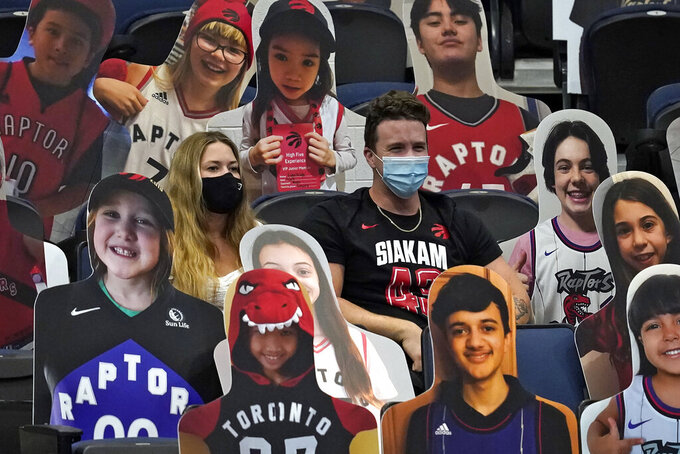 Toronto Raptors fans sits with cardboard cutouts of fans during the second half of an NBA basketball game against the Indiana Pacers Sunday, May 16, 2021, in Tampa, Fla. (AP Photo/Chris O'Meara)