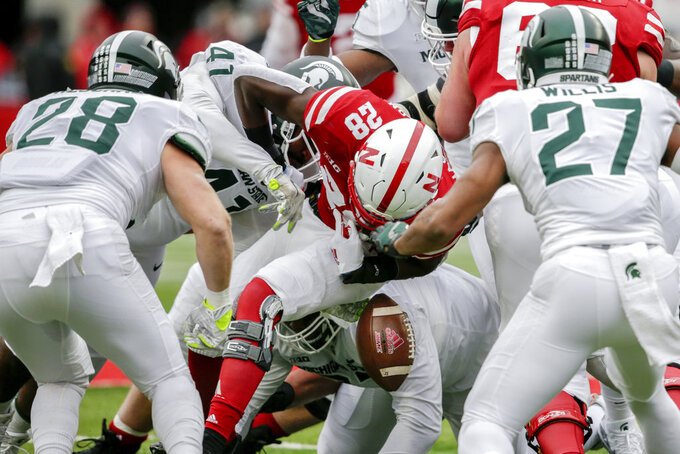 Nebraska running back Maurice Washington (28) fumbles the ball as he is surrounded by Michigan State linebacker Jon Reschke (28), safety Khari Willis (27) and defensive tackle Gerald Owens (41), during the first half of an NCAA college football game in Lincoln, Neb., Saturday, Nov. 17, 2018. Nebraska recovered the fumble. (AP Photo/Nati Harnik)