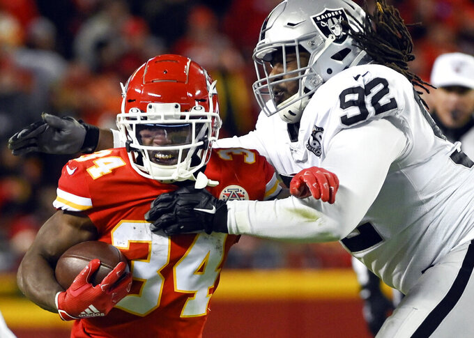 FILE - In this Dec. 1, 2019, file photo, Kansas City Chiefs running back Darwin Thompson (34) gets past Oakland Raiders defensive tackle P.J. Hall (92) during the second half of an NFL football game in Kansas City, Mo., The Minnesota Vikings have acquired Hall from the Raiders for a conditional seventh-round draft pick in 2021. Hall provides reinforcement for the interior for the Vikings after the opt-out by expected starter Michael Pierce. (AP Photo/Reed Hoffmann, File)