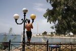 A man trains on a lighting column during a warm day in Piraeus, near Athens, Wednesday, May 20, 2020. Public beaches were reopened last weekend amid heatwave temperatures, with strict distancing rules imposed by the government, but crowding did occur on buses from Athens to the nearby coast. Travel to the Greek islands remains broadly restricted due to the coronavirus pandemic. (AP Photo/Thanassis Stavrakis)