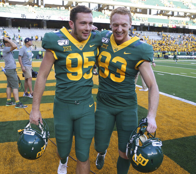 Baylor place kicker John Mayers, left, walks off with teammate Russell Morrison after defeating Iowa State in the second half of an NCAA college football game, Saturday, Sept. 28, 2019, in Waco, Texas. Mayers had the game winning field goal late in the game. (Rod Aydelotte/Waco Tribune-Herald via AP)
