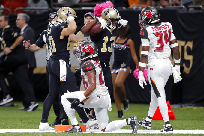 New Orleans Saints wide receiver Michael Thomas (13) celebrates his touchdown with wide receiver Austin Carr (80) in front of Tampa Bay Buccaneers cornerback Vernon III Hargreaves (28) and safety Mike Edwards (34) in the first half of an NFL football game in New Orleans, Sunday, Oct. 6, 2019. (AP Photo/Bill Feig)
