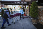 Employees deliver a body at Daniel J. Schaefer Funeral Home, Thursday, April 2, 2020, in the Brooklyn borough of New York. The company is equipped to handle 40-60 cases at a time. But amid the coronavirus pandemic, it was taking care of 185 Thursday morning. (AP Photo/John Minchillo)
