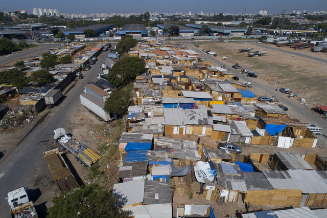 Shacks fill the Jardim Julieta squatter camp in Sao Paulo, Brazil, Thursday, July 23, 2020. The coronavirus had just hit the city when this parking lot for trucks became a favela, with dozens of shacks. Since the first wave of residents in mid-March, hundreds of families joined, with most having been evicted during the pandemic. (AP Photo/Andre Penner)