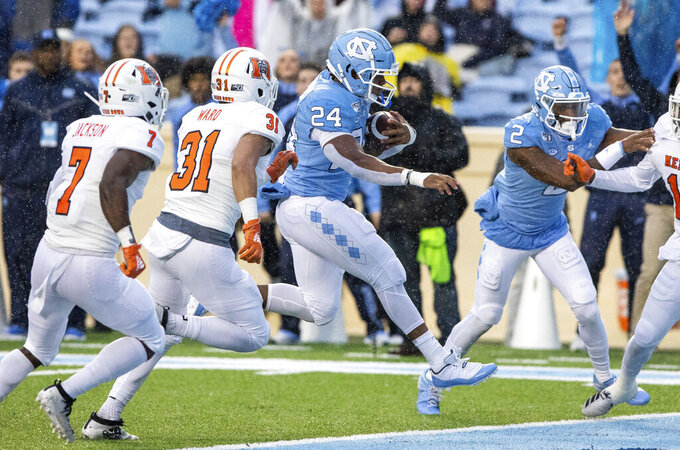 North Carolina's Antonio Williams (24) scores a touchdown ahead of Mercer's Eric Jackson (7) and Luke Ward (31) during the first half of an NCAA college football game in Chapel Hill, N.C., Saturday, Nov. 23, 2019. (AP Photo/Ben McKeown)