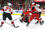 Carolina Hurricanes goalie Petr Mrazek (34), of the Czech Republic, blocks New Jersey Devils' Stefan Noesen (23) while Hurricanes' Justin Faulk and Devils' Nathan Bastian struggle at right during the first period of an NHL hockey game in Raleigh, N.C., Thursday, April 4, 2019. (AP Photo/Gerry Broome)