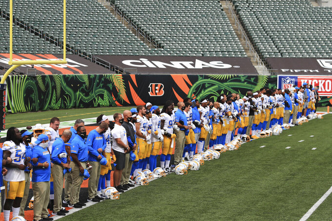 "The Los Angeles Chargers stand arm-in-arm as ""Lift Every Voice and Sing"" is played before an NFL football game against the Cincinnati Bengals, Sunday, Sept. 13, 2020, in Cincinnati. (AP Photo/Aaron Doster)"