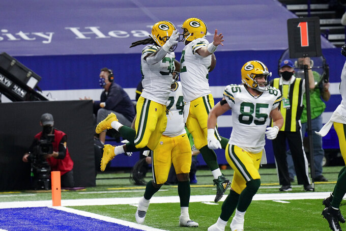 Green Bay Packers running back Jamaal Williams (30) and quarterback Aaron Rodgers (12) celebrate a touchdown during the first half of an NFL football game against the Indianapolis Colts, Sunday, Nov. 22, 2020, in Indianapolis. (AP Photo/AJ Mast)