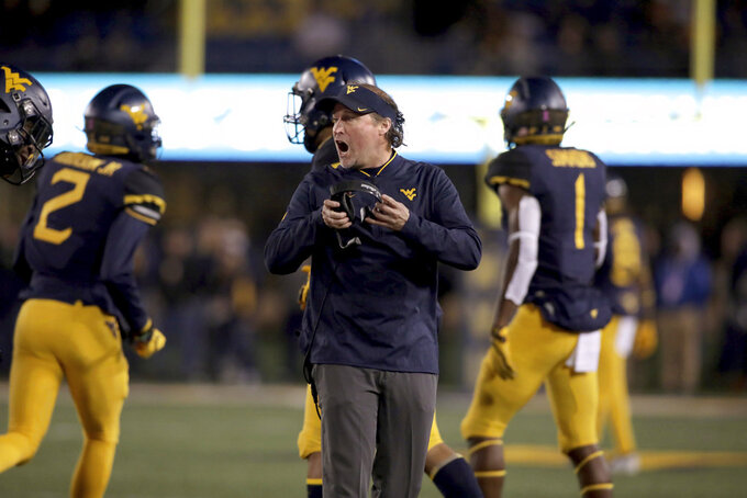 West Virginia head coach Dana Holgorsen, center, shouts directions to his players during the first half of an NCAA college football game against Baylor, Thursday, Oct. 25, 2018, in Morgantown, W.Va. (AP Photo/Raymond Thompson)
