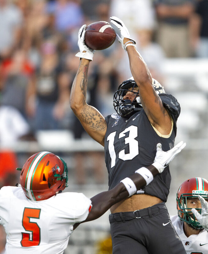 Central Florida wide receiver Gabriel Davis (13) grabs a touchdown pass on Florida A&M defensive backs Markquese Bell (5) and Troy Hilton, right, during the first half of an NCAA college football game Thursday, Aug. 29, 2019, in Orlando, Fla. (AP Photo/Willie J. Allen Jr.)