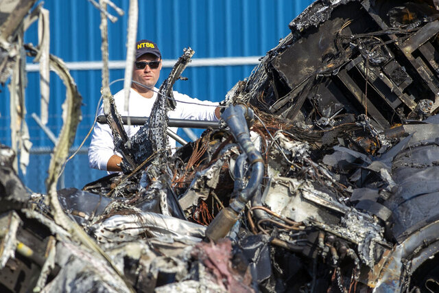 A member of the National Transportation Safety Board looks at the wreckage of a plane that Dale Earnhardt Jr., his wife and daughter and two pilots and a dog were on when it crash landed at the Elizabethton Municipal Airport in Elizabethton, Tenn., in a Friday, Aug. 16, 2019 file photo.The National Transportation Safety Board said Wednesday, Sept. 23, 2020 a pilot's inability to maintain proper airspeed and the flight crew's decision to continue an unstable approach for landing likely caused the crash of a small plane carrying race car driver Dale Earnhardt Jr. and his family in 2019.  (David Crigger/Bristol Herald Courier via AP, File)