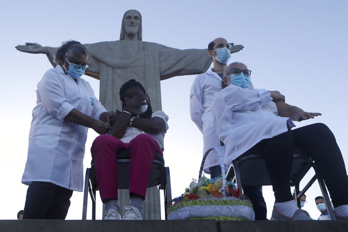 CORRECTS DATE FROM 28 TO 18 - Terezinha da Conceicao, sitting left, and Dulcinea da Silva Lopes, sitting right, become the first women to receive the COVID-19 vaccine produced by China's Sinovac Biotech Ltd, during the start of the vaccination program in front of the Christ the Redeemer statue in Rio de Janeiro, Brazil, Monday, Jan. 18, 2021. (AP Photo/Bruna Prado)