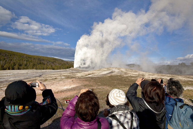 FILE - In this May 21, 2011, file photo, tourists photograph Old Faithful erupting on schedule late in the afternoon in Yellowstone National Park, Wyo. A woman has suffered burns after falling into a thermal feature at Yellowstone National Park, which is closed because of the coronavirus pandemic. Officials say she was reportedly backing up while taking photos Tuesday, May 12, 2020, and fell into a hot spring or hole where hot gases emerge near Old Faithful geyser. (AP Photo/Julie Jacobson, File)