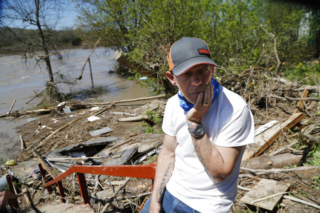 Dan Dionne looks over his former deck outside his home, Wednesday, May 20, 2020, in Edenville, Mich. Some people living along two mid-Michigan lakes and parts of a river have been evacuated following several days of heavy rain that produced flooding and put pressure on dams in the area returned to the area to survey the damage. (AP Photo/Carlos Osorio)