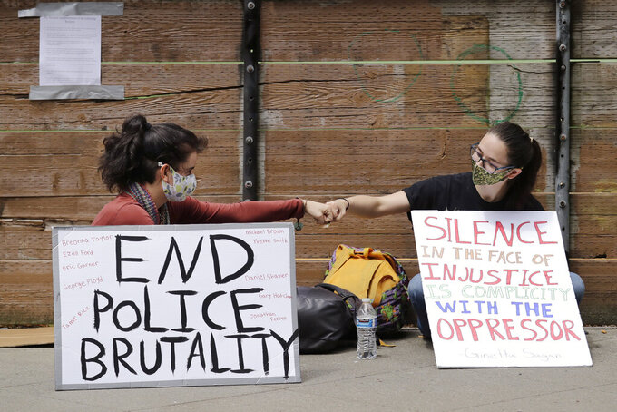 Protesters Kaylee Gore, left, and Amanda Barnes exchange fist bumps as they sit with signs protesting police actions, Thursday, June 4, 2020, in Seattle, following protests over the death of George Floyd in Minneapolis. Seattle's police chief says officers' badge numbers will be prominently displayed following complaints that black bands obscured the digits. (AP Photo/Elaine Thompson)