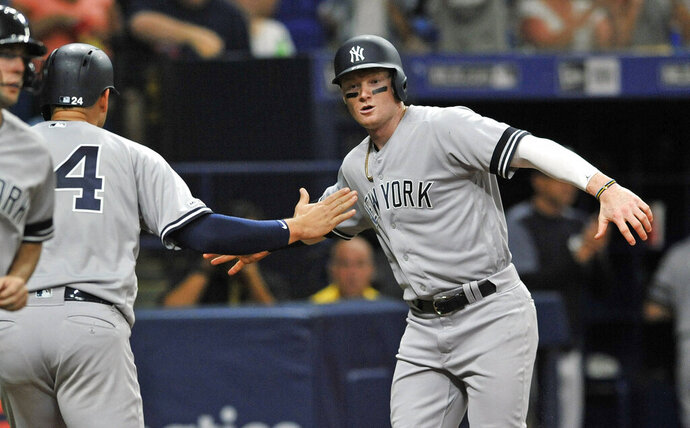 New York Yankees' Gary Sanchez (24) and Clint Frazier celebrate after scoring on Gio Urshela's two-run single off Tampa Bay Rays reliever Emilo Pagan during the sixth inning of a baseball game Friday, May 10, 2019, in St. Petersburg, Fla. (AP Photo/Steve Nesius)wb