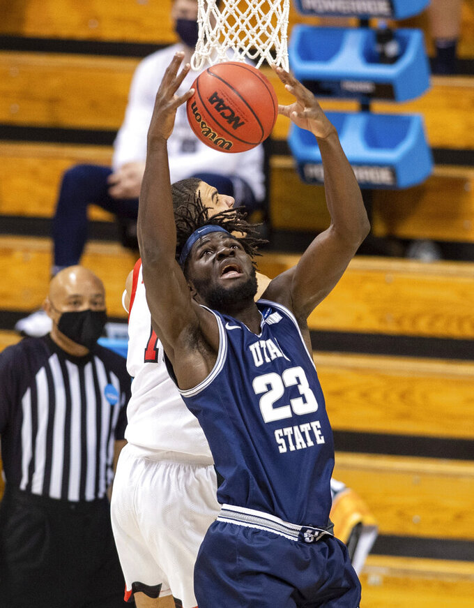 Utah State center Neemias Queta (23) pulls in a rebound during the second half of a first round game against Texas Tech in the NCAA men's college basketball tournament, Friday, March 19, 2021, at Assembly Hall in Bloomington, Ind. (AP Photo/Doug McSchooler)