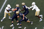 Navy quarterback Zach Abey (9) rushes the ball past Tulsa safety McKinley Whitfield, from left, Navy offensive tackle Andrew Wood, Navy wide receiver Mychal Cooper and Tulsa cornerback Reggie Robinson II in the first half of an NCAA college football game, Saturday, Nov. 17, 2018, in Annapolis, Md. (AP Photo/Patrick Semansky)