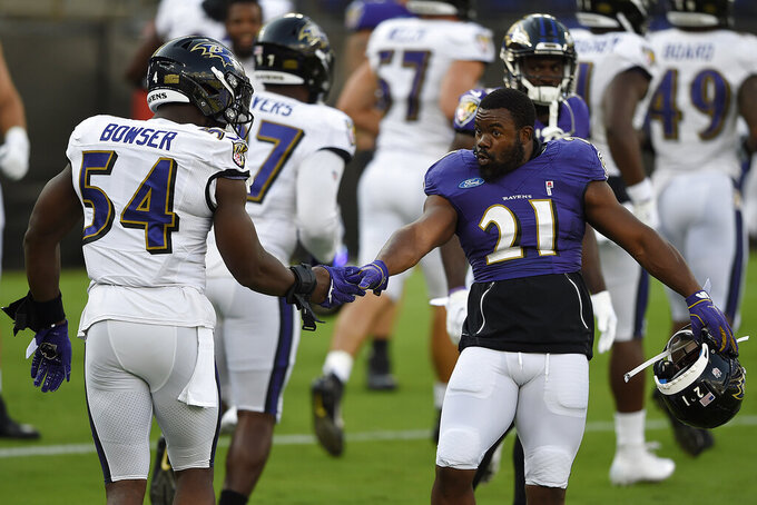 FILE - Baltimore Ravens Mark Ingram II, right, shakes hands with Tyrus Bowser during an NFL football training camp practice, Saturday, Aug. 29, 2020, in Baltimore, Md. They'll be playing Sunday in an empty stadium, facing a Cleveland Browns team with a new coaching staff that's provided no clue how they plan to employ a revamped offense. (AP Photo/Gail Burton, FILE)