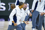 Michigan head coach Juwan Howard, front, is restrained after being ejected from the game in the second half of an NCAA college basketball game against Maryland at the Big Ten Conference tournament in Indianapolis, Friday, March 12, 2021. (AP Photo/Michael Conroy)