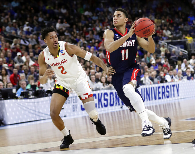 Belmont 's Kevin McClain (11) drives around Maryland 's Aaron Wiggins (2) during the first half of a first round men's college basketball game in the NCAA Tournament in Jacksonville, Fla., Thursday, March 21, 2019. (AP Photo/John Raoux)
