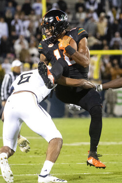 Miami wide receiver Lawrence Cager makes a catch and is tackled by Georgia Tech defensive back Lamont Simmons during the first quarter of an NCAA college football game Saturday, Nov. 10, 2018, in Atlanta. (AP Photo/John Amis)