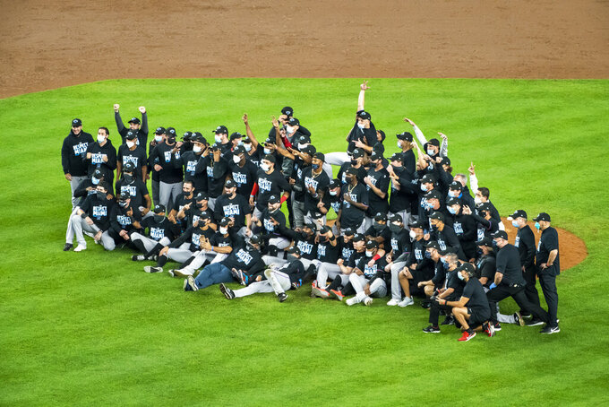The Miami Marlins gather for a photograph on the pitcher's mound after clinching a playoff berth when they won in the 10th inning of a baseball game against the New York Yankees at Yankee Stadium, Friday, Sept. 25, 2020, in New York. (AP Photo/Corey Sipkin)