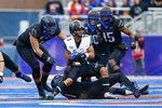 Hawaii wide receiver Jason-Matthew Sharsh, center, is pulled down by Boise State defensive back Tyreque Jones, bottom, as Boise State linebacker Curtis Weaver, left, and Boise State cornerback Jalen Walker, right, move in to help with the tackle during the first half of an NCAA college football game for the Mountain West Championship Saturday, Dec. 7, 2019, in Boise, Idaho. (AP Photo/Steve Conner)