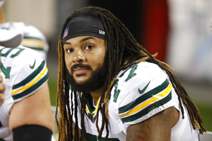 """FILE - In this Thursday, Sept. 5, 2019 file photo, Green Bay Packers offensive tackle Billy Turner sits on the bench during an NFL football game against the Chicago Bears in Chicago. Green Bay Packers right guard William """"Billy"""" Turner's perspective on life was bleak and negative after he was cut by the Dolphins in October 2016. But more than three years later, Turner's outlook has changed, and the 6-foot-5, 310-pound guard's conscious mission to spread positive energy has become a driving force behind the Packers' success this season.(AP Photo/Charles Rex Arbogast, File)"""