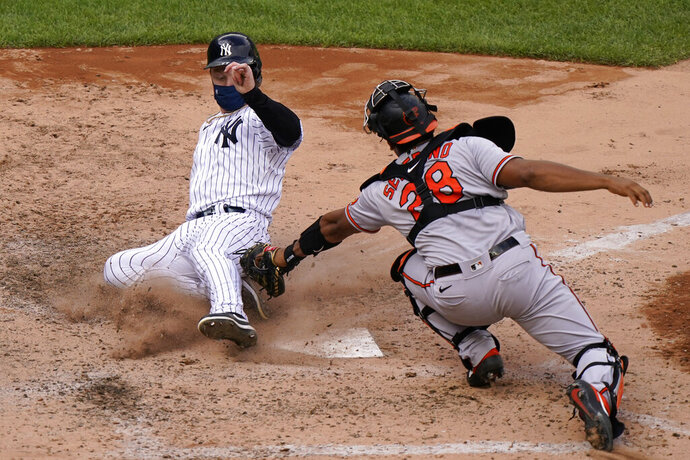New York Yankees' Clint Frazier, left, is safe scoring ahead of a tag by Baltimore Orioles catcher Pedro Severino (28) on pinch hitter Gleyber Torres's two-run double during the eighth inning of a baseball game, Sunday, Sept. 13, 2020, at Yankee Stadium in New York. (AP Photo/Kathy Willens)