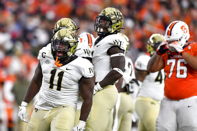 Wake Forest defensive lineman Miles Fox (11) and defensive end Jacorey Johns (4) celebrate a sack on Syracuse quarterback Garrett Shrader during the second half of an NCAA college football game in Syracuse, N.Y., Saturday, Oct. 9, 2021. (AP Photo/Adrian Kraus)