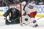 San Jose Sharks goaltender Aaron Dell, left, defends against a shot by Columbus Blue Jackets center Pierre-Luc Dubois (18) during the second period of an NHL hockey game in San Jose, Calif., Thursday, Jan. 9, 2020. (AP Photo/Jeff Chiu)
