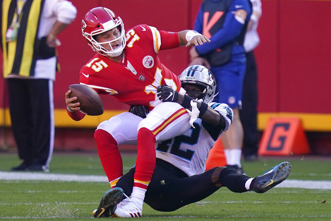 Kansas City Chiefs quarterback Patrick Mahomes, left, is sacked by Carolina Panthers safety Sam Franklin during the second half of an NFL football game in Kansas City, Mo., Sunday, Nov. 8, 2020. (AP Photo/Orlin Wagner)