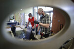 Glass installers Nick Trueblood, of Clinton, Mass., left, and Michael Cane, of Burlington, Mass., right, install a plastic barrier, Thursday, May 21, 2020, at a security desk at the entrance to a dormitory, at Boston University, in Boston. Boston University is among a growing number of universities making plans to bring students back to campus this fall, but with new measures meant to keep the coronavirus at bay. (AP Photo/Steven Senne)