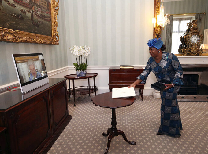 Britain's Queen Elizabeth II appears on a screen by videolink from Windsor Castle, where she is in residence, during a virtual audience to receive Her Excellency Sara Affoue Amani, the Ambassador of Cote d'Ivoire, at Buckingham Palace, London, Tuesday April 27, 2021. (Yui Mok/Pool via AP)
