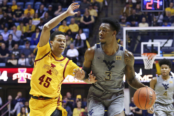 West Virginia forward Gabe Osabuohien (3) looks to pass the ball as he is defended by Iowa State guard Rasir Bolton (45) during the second half of an NCAA college basketball game Wednesday, Feb. 5, 2020, in Morgantown, W.Va. (AP Photo/Kathleen Batten)