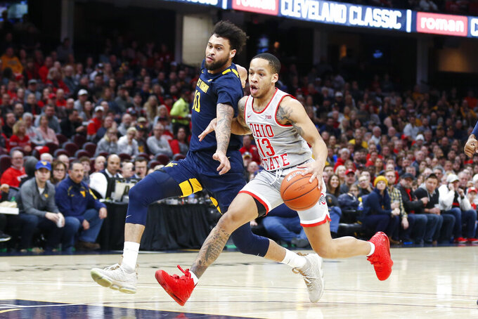 Ohio State's CJ Walker (13) drives on West Virginia's Jermaine Haley (10) during the first half of an NCAA college basketball game Sunday, Dec. 29, 2019, in Cleveland. West Virginia defeated Ohio State 67-59. (AP Photo/Ron Schwane)