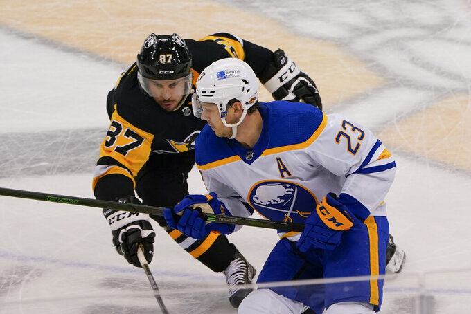 Pittsburgh Penguins' Sidney Crosby (87) chases Buffalo Sabres' Sam Reinhart (23) during the third period of an NHL hockey game, Thursday, March 25, 2021, in Pittsburgh. (AP Photo/Keith Srakocic)