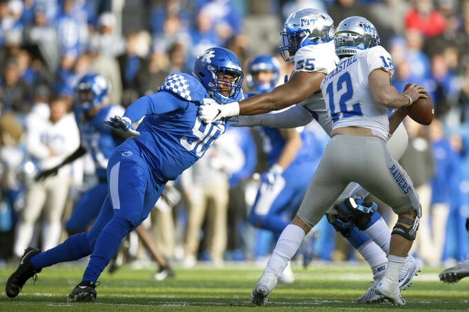 Kentucky defensive end T.J. Carter (90) pressures Middle Tennessee quarterback Brent Stockstill (12) during the second half of an NCAA college football game in Lexington, Ky., Saturday, Nov. 17, 2018. (AP Photo/Bryan Woolston)