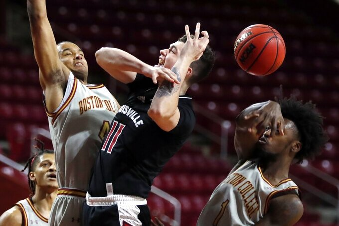 Louisville's Brad Colbert (4) blocks a shot by Boston College's Abe Atiyeh (11) during the first half of an NCAA college basketball game, Saturday, Jan. 2, 2021, in Boston. (AP Photo/Michael Dwyer)