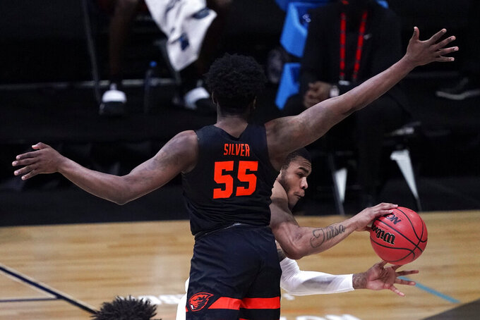 Houston forward Reggie Chaney passes around Oregon State guard Tariq Silver (55) during the first half of an Elite 8 game in the NCAA men's college basketball tournament at Lucas Oil Stadium, Monday, March 29, 2021, in Indianapolis. (AP Photo/Darron Cummings)