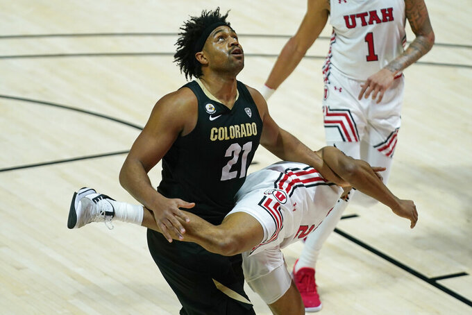 Colorado forward Evan Battey (21) battles for position under the basket with Utah guard Ian Martinez (2) in the first half during an NCAA college basketball game Monday, Jan. 11, 2021, in Salt Lake City. (AP Photo/Rick Bowmer)