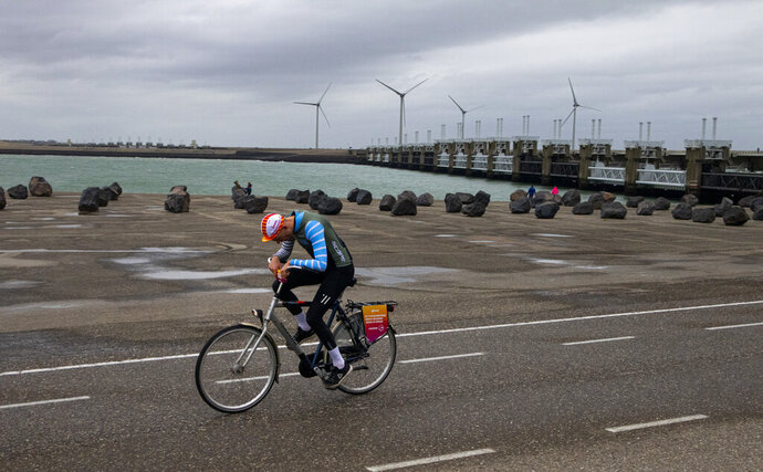 A competitor battles gale force winds during the Dutch Headwind Cycling Championships on the storm barrier Oosterscheldekering, rear, near Neeltje Jans, south-western Netherlands, Sunday, Feb. 9, 2020. (AP Photo/Peter Dejong)