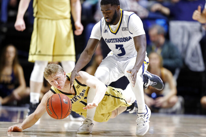 Wofford guard Ryan Larson (11) battles for the loose ball with Chattanooga guard David Jean-Baptiste (3) during the first half of an NCAA college basketball game Thursday, Feb. 28, 2019, in Chattanooga, Tenn. (AP photo/Wade Payne)