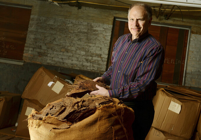 Eric Newman, President of J.C. Newman Cigar Company, poses for a photograph Friday, Dec. 19, 2014 along with a bail of Cuban tobacco that was purchased before the 1960 embargo. One of the historic sweeping changes in the United States' policy toward Cuba that President Barrack Obama announced on Wednesday was allowing U.S. citizens visiting the island nation to bring up to $100 in tobacco products back with them. (Chris Urso/Tampa Bay Times via AP)