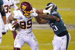Washington Football Team's Chase Young (99) tries to get past Philadelphia Eagles' Boston Scott (35) after recovering a loose snap during the second half of an NFL football game, Sunday, Jan. 3, 2021, in Philadelphia. (AP Photo/Chris Szagola)