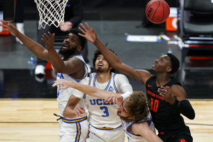 UCLA's Cody Riley, from left, Johnny Juzang, Jake Kyman and Oregon State's Warith Alatishe vie for a rebound during the first half of an NCAA college basketball game in the quarterfinal round of the Pac-12 men's tournament Thursday, March 11, 2021, in Las Vegas. (AP Photo/John Locher)