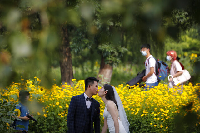 FILE - People wearing face masks pass by newlyweds kissing as they posing for wedding photos at the Olympic Forest Park in Beijing on July 2, 2020. Now that weddings have slowly cranked up under a patchwork of ever-shifting restrictions, horror stories from vendors are rolling in. Many are desperate to work after the coronavirus put an abrupt end to their incomes and feel compelled to put on their masks, grab their cameras and hope for the best. (AP Photo/Andy Wong)