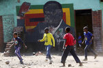 FILE - In this Friday, Sept. 6, 2019, file photo, children play soccer next to a defaced portrait of former Zimbabwean president Robert Mugabe in Harare, Zimbabwe. After 16 years in journalistic exile, Andrew Meldrum returned to Zimbabwe, the country where he worked as a journalist for 23 years until he was expelled by Mugabe's government. (AP Photo/Tsvangirayi Mukwazhi, File)